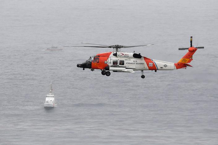 A U.S. Coast Guard helicopter flies over boats searching the area where a boat capsized off the San Diego coast on May 2.