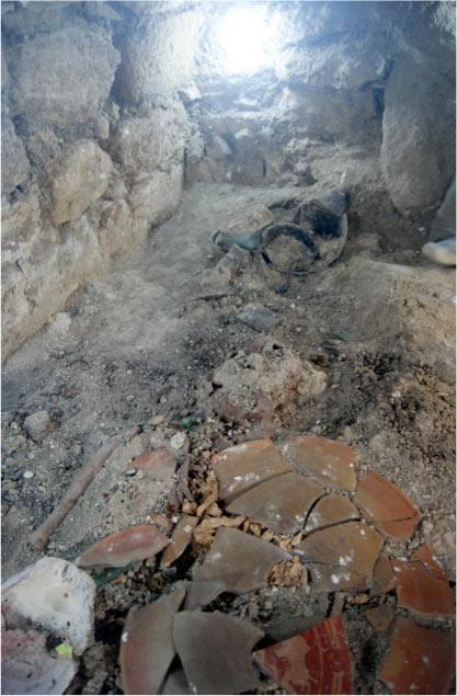 The burial chamber of what archaeologists think belonged to Mayan warrior queen K'abel. The queen's skull is above the plate fragments. (El Peru Waka Regional Archaeological Project)