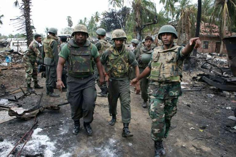 Government soldiers in 2009 inspect a civil war battle zone