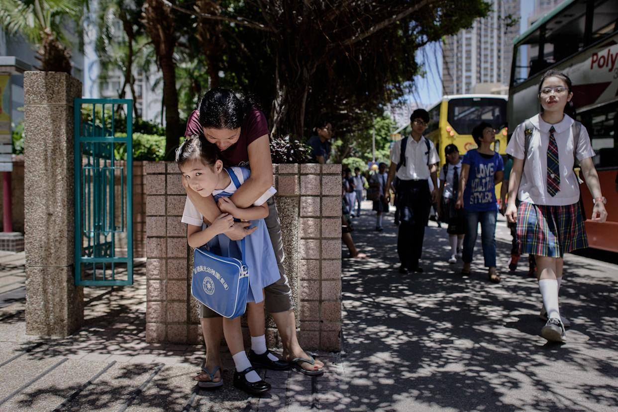 Maia, 5, gets a hug from her nanny on her way to school outside her home in Hong Kong on June 18, 2013.