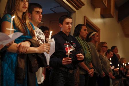 People hold candles during a prayer vigil for victims of the Franklin Regional High School stabbing rampage, at Mother of Sorrows Roman Catholic Church in Murrysville, Pennsylvania April 9, 2014. REUTERS/Shannon Stapleton