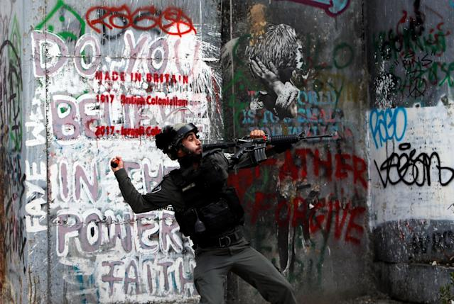 <p>An Israeli border police officer throws a sound grenade toward Palestinian demonstrators in Bethlehem in the occupied West Bank during a protest against the U.S. Embassy's move to Jerusalem on May 14, 2018. (Photo: Mussa Qawasma/Reuters) </p>