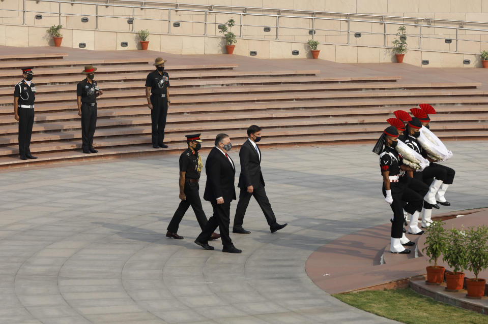 U.S. Secretary of State Mike Pompeo, foreground, and Secretary of Defence Mark Esper arrive to pay their tributes at the National War Memorial in New Delhi, India, Tuesday, Oct. 27, 2020. In talks on Tuesday with their Indian counterparts, Pompeo and Esper are to sign an agreement expanding military satellite information sharing and highlight strategic cooperation between Washington and New Delhi with an eye toward countering China. (Adnan Abidi/Pool via AP)