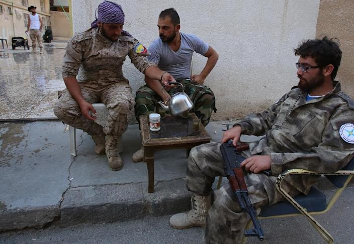 Members of the Assyrian Gozarto Protection Forces (GPF), consisting of Sutoro militia, a pro-government Syriac Christian movement, and other Assyrian fighters resting and drinking tea (AFP Photo/Youssef Karwashan )