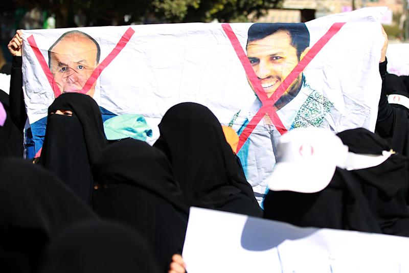 Yemeni women hold a banner bearing red crosses on portraits of Yemeni former president Abdrabuh Mansur Hadi (L) and Shiite Huthi movement's leader Abdul-Malik al-Huthi during a rally against Huthi rebels on January 24, 2015 in Sanaa (AFP Photo/Mohammed Huwais)