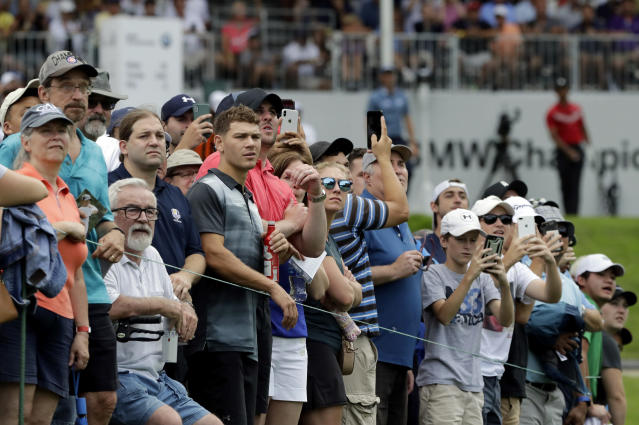 Fans watch Tiger Woods' tee shot on the 13th hole during the final round of the BMW Championship golf tournament at Medinah Country Club, Sunday, Aug. 18, 2019, in Medinah, Ill. (AP Photo/Nam Y. Huh)