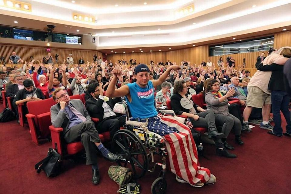 Chaunce O 'Connor, gives a thumbs-down signal while the rest of the audience has their hands up in support, during a heated debate on President Donald Trump's immigration policy at the Feb. 17, 2017 meeting of the Miami-Dade County Commission.