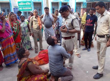 Relatives of the victims of a mob lynching incident speak to a police officer as they mourn outside a hospital in Chapra