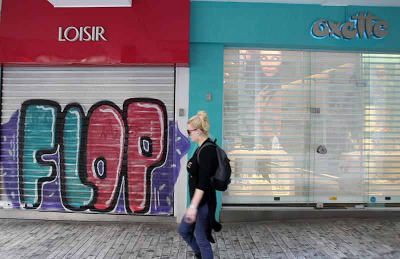 A pedestrian passes closed shops in Ermou street, Athens' main shopping district as shopkeepers shut down for the 24-hour nationwide general strike on Thursday, Oct. 18, 2012. Labor unions in recession-hobbled Greece are holding another general strike against a new harsh austerity program, as European leaders beset by a deep debt crisis and economic stagnation gather for a summit meeting in Brussels. (AP Photo/Thanassis Stavrakis)