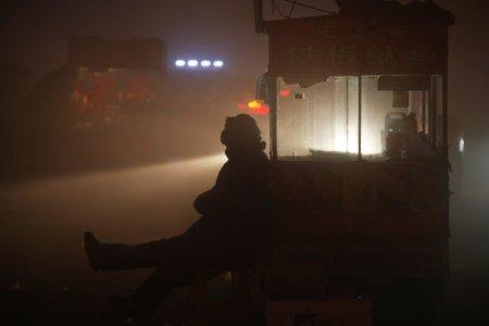 FILE PHOTO: A street food vendor waits for customers as heavy smog blankets Shengfang, in Hebei province, on an extremely polluted day with red alert issued, China December 19, 2016. REUTERS/Damir Sagolj