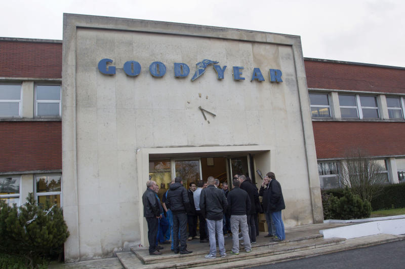 Workers of the Goodyear tire factory gather at an entrance to the plant in Amiens, northern France, Monday, Jan. 6, 2014. Two Goodyear managers, production manager Michel Dheilly and Human Resources director Bernard Glesser, were blocked from leaving the plant on Monday, with angry workers demanding more money in exchange for the inevitable loss of their jobs. (AP Photo/Michel Euler)