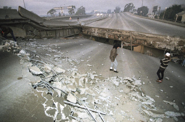FILE - In this Jan. 17, 1994 file photo, Interstate 10, the Santa Monica Freeway, split and collapsed over La Cienega Boulevard following the Northridge quake in the predawn hours in Los Angeles. Twenty-five years ago this week, a violent, pre-dawn earthquake shook Los Angeles from its sleep, and sunrise revealed widespread devastation, with dozens killed and $25 billion in damage. (AP Photo/Eric Draper, File)