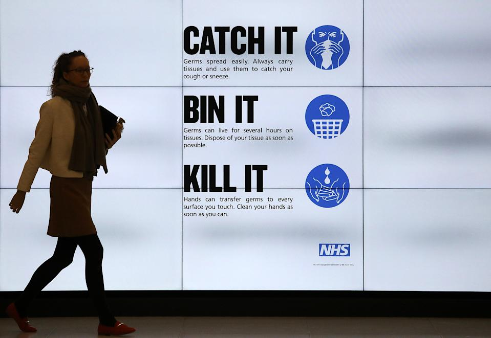 An NHS catch it, bin it, kill it sign on TV screens in the entrance to the QEII Centre in London. (Photo by Philip Toscano/PA Images via Getty Images)
