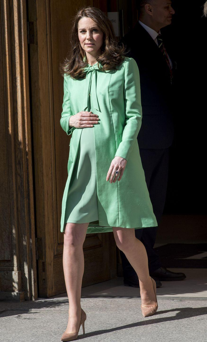 """<p>She would, however, always return to the trusted coat-dress combo. In this striking <a href=""""https://www.cosmopolitan.com/uk/fashion/celebrity/a19559081/kate-middleton-mint-green-coat/"""" rel=""""nofollow noopener"""" target=""""_blank"""" data-ylk=""""slk:green ensemble"""" class=""""link rapid-noclick-resp"""">green ensemble</a>, the overcoat's open design revealed her bump (and a beautiful matching dress). </p>"""