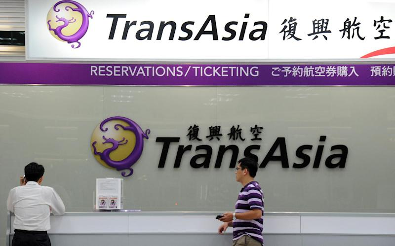 Journalists wait in front of a TransAsia reservations desk at Sungshan airport in Taipei, on July 23, 2014 (AFP Photo/Sam Yeh)