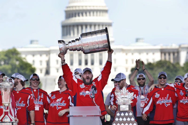 FILE - In this June 12, 2018, file photo, Washington Capitals' Alex Ovechkin, of Russia, holds up the Stanley Cup trophy during the NHL hockey team's Stanley Cup victory celebration at the National Mall in Washington. The U.S. Capitol rises in the background. A person with direct knowledge of the decision says the Capitals will go to the White House on Monday, March 25, 2019, to celebrate their Stanley Cup championship. The person spoke to The Associated Press on condition of anonymity Tuesday, March 19, 2019, because the team had not announced the decision.(AP Photo/Jacquelyn Martin, File)