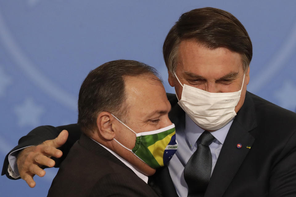 Brazil's President Jair Bolsonaro, wearing a mask to curb the spread of COVID-19, greets Health Minister Gen. Eduardo Pazuelo, left, during a ceremony at the Planalto Presidential Palace, in Brasilia, Brazil, Wednesday, Sept. 16, 2020. After almost four months overseeing the COVID-19 response as interim health minister, Gen. Eduardo Pazuello will finally be made a full minister. (AP Photo/Eraldo Peres)