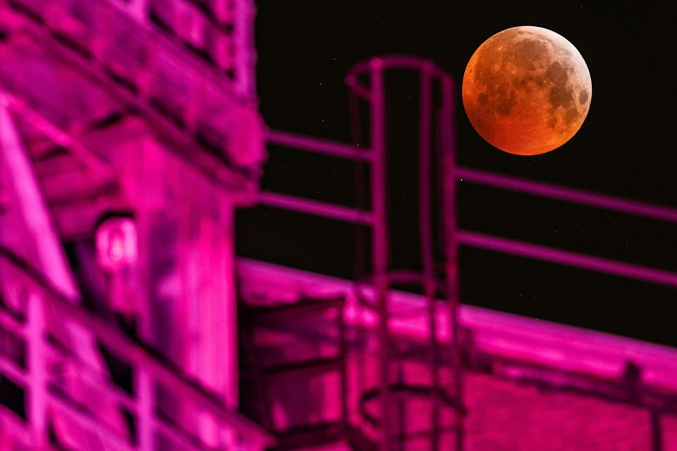A picture taken on January 21, 2019 in Duisburg shows a view of the Super Blood Moon above an industrial plant during a lunar eclipse. (Photo by Marcel Kusch / dpa / AFP) / Germany OUT        (Photo credit should read MARCEL KUSCH/DPA/AFP via Getty Images)