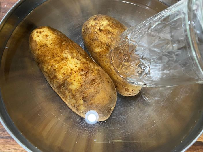 Potatoes sitting in a bowl of water while holding the potatoes in a glass