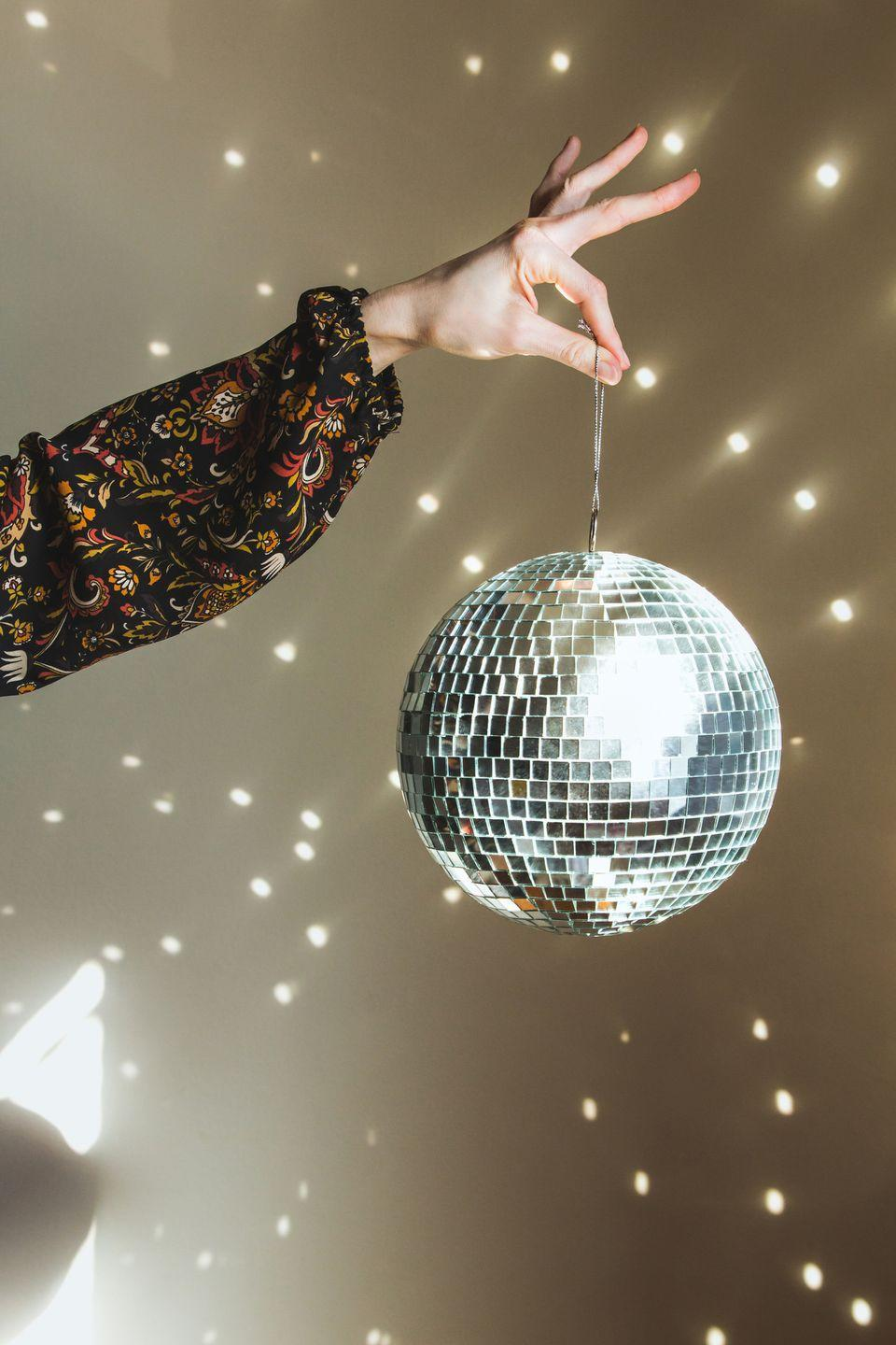 """<p>If you're looking to dance your way into the New Year, there's nothing more groovy than a disco-themed party, complete with a funky '70s music playlist, gold maxi dresses and platform shoes, and of course, the all-essential sparkly <a href=""""https://www.amazon.com/Rhode-Island-Novelty-Mirror-Order/dp/B004DIVTIC/ref=sr_1_8?keywords=disco+ball&qid=1575399629&sr=8-8&tag=syn-yahoo-20&ascsubtag=%5Bartid%7C10055.g.30105731%5Bsrc%7Cyahoo-us"""" rel=""""nofollow noopener"""" target=""""_blank"""" data-ylk=""""slk:disco ball"""" class=""""link rapid-noclick-resp"""">disco ball</a> to get the vibes going on the dance floor. </p>"""