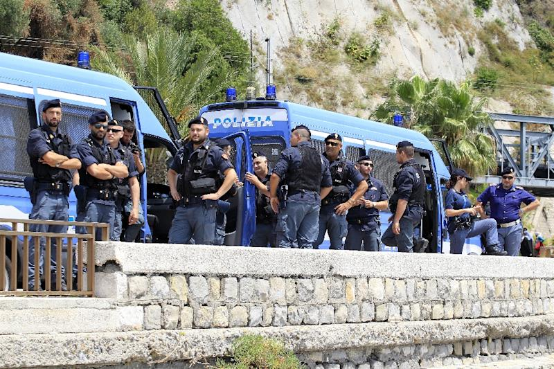 Italian police officers stand near where migrants are settled on a rocks off the coast of Ventimiglia, Italy, on June 14, 2015 (AFP Photo/Jean-Christophe Magnent)
