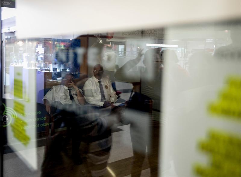 Security guards sit inside a closed United Airlines office as customers waiting outside for information about ticket sales are reflected in the window in Caracas, Venezuela, Friday, Jan. 24, 2014. Delta, American Airlines and Panama's Copa Airlines were also among carriers whose offices were either closed or had halted sales on Friday after the government devalued the local currency for flights abroad. (AP Photo/Alejandro Cegarra)