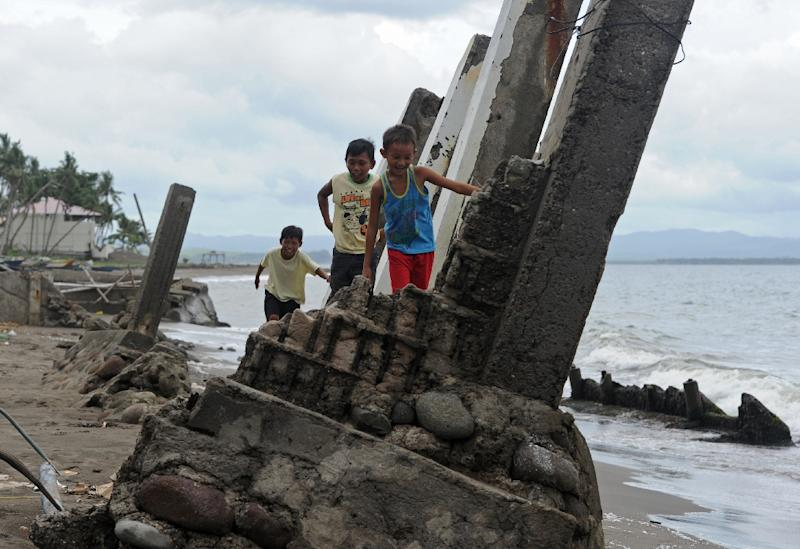 Young boys walk over remains of a house destroyed at the height of typhoon Haiyan, in a coastal village near Tacloban City, Leyte province of central Philippines (AFP Photo/Ted Aljibe)