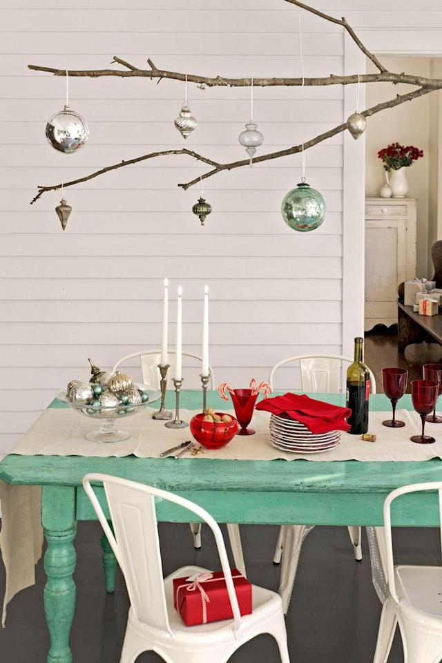 """<p>Branch out from conventional tablescapes by using an extra-long tree limb as a platform for displaying ornaments. Simply knot lengths of twine around the branch and hang it from a row of five or six ceiling hooks.</p><p><a class=""""link rapid-noclick-resp"""" href=""""https://www.amazon.com/s/ref=nb_sb_noss_1?url=search-alias%3Daps&field-keywords=christmas+ornaments&tag=syn-yahoo-20&ascsubtag=%5Bartid%7C10050.g.644%5Bsrc%7Cyahoo-us"""" rel=""""nofollow noopener"""" target=""""_blank"""" data-ylk=""""slk:SHOP ORNAMENTS"""">SHOP ORNAMENTS</a></p>"""