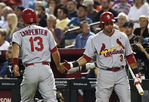 St. Louis Cardinals' Matt Carpenter (13) shakes hands with teammate Carlos Beltran (3) after scoring a run against the Arizona Diamondbacks in the first inning during a baseball game Monday, April 1, 2013, in Phoenix. (AP Photo/Ross D. Franklin)