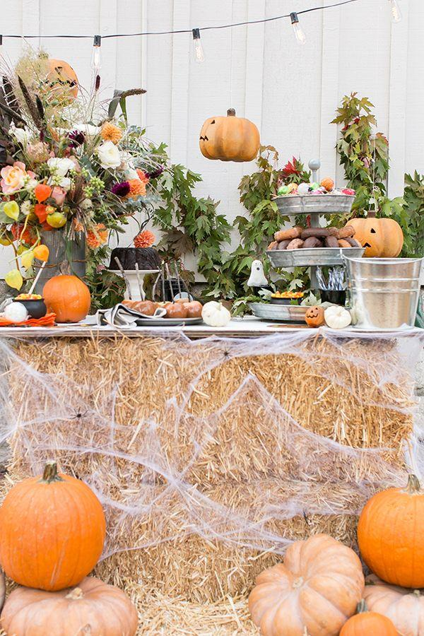 <p>Sugar & Charm set up the ultimate outdoor Halloween buffet by using cobweb-covered hay as the table. Then, hang some string lights, surround the spread with pumpkins, add a Halloween-inspired bouquet, and call it a day.</p>