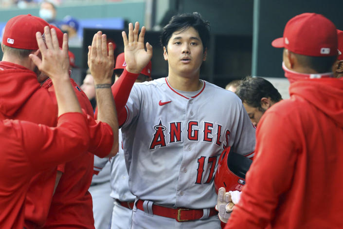 Los Angeles Angels starting pitcher Shohei Ohtani (17) is greeted in the dugout after scoring in the first inning during a baseball game against the Texas Rangers on Monday, April 26, 2021, in Arlington, Texas. (AP Photo/Richard W. Rodriguez)
