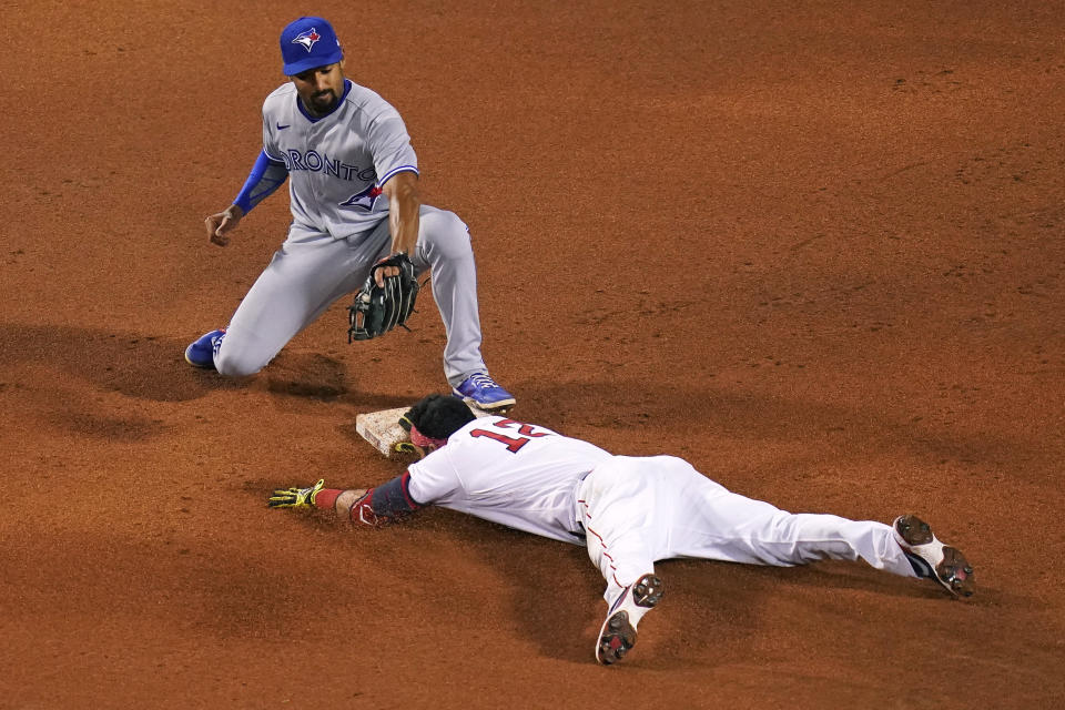 Boston Red Sox's Marwin Gonzalez (12) beats the tag by Toronto Blue Jays second baseman Marcus Semien while sliding into second with a double during the sixth inning of a baseball game at Fenway Park, Wednesday, April 21, 2021, in Boston. (AP Photo/Charles Krupa)