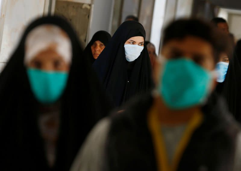 Iraqi people wear protective masks, following the outbreak of the new coronavirus, at a hospital in Najaf