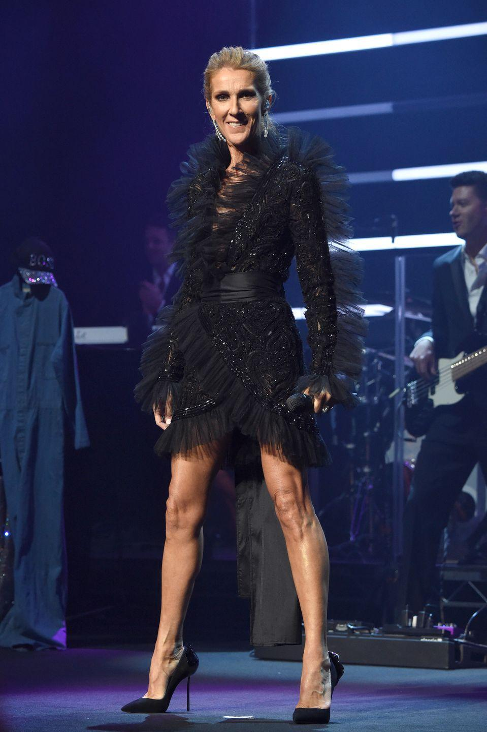 """<p>For her """"Courage"""" world tour announcement, Celine chose a black wrap dress with intricate beading and a pair of black pumps. </p>"""