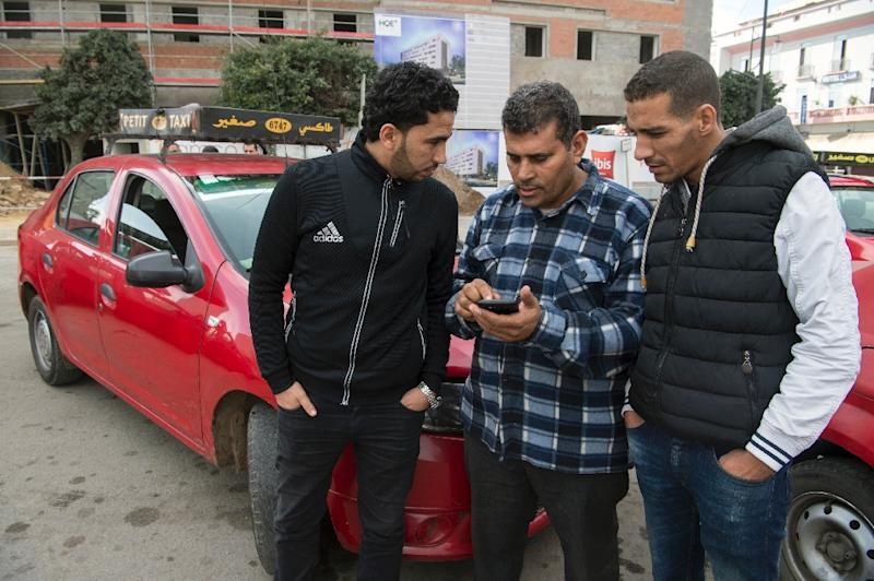 Moroccan taxi drivers check the Uber app as they wait for customers in Casablanca (AFP Photo/Fadel Senna)