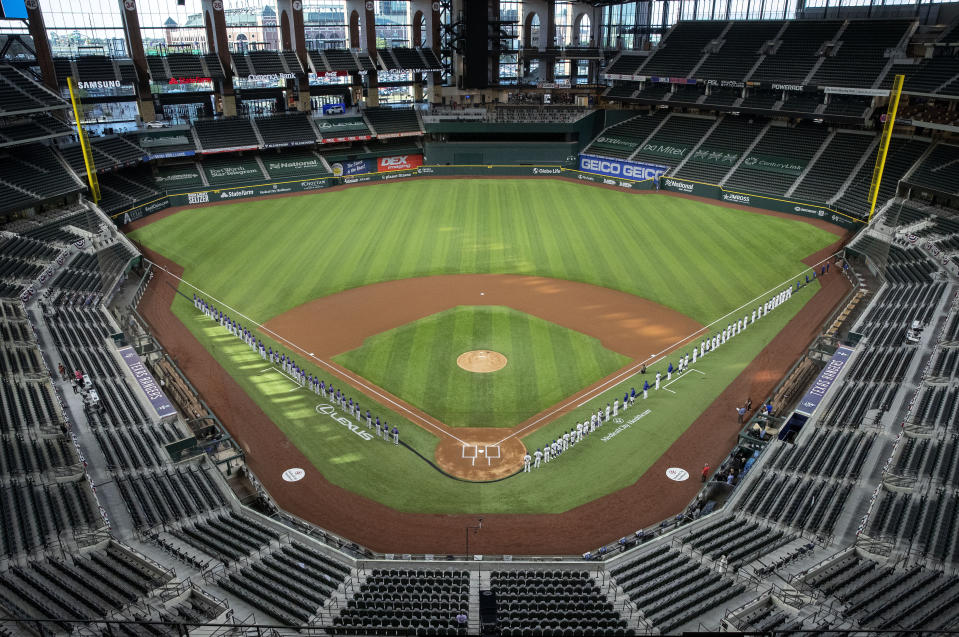 The Colorado Rockies and the Texas Rangers hold a strip of black fabric as they observe a moment of silence in recognition of the Black Lives Matter movement before an opening day baseball game Friday, July 24, 2020, in Arlington, Texas. (AP Photo/Jeffrey McWhorter)