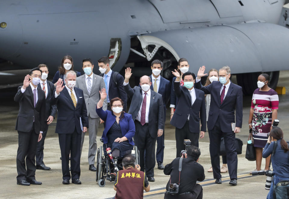 Taiwan's Foreign Minister Joseph Wu, fourth from right, waves with U.S. senators to his right Democratic Sen. Christopher Coons of Delaware, a member of the Foreign Relations Committee, Democratic Sen. Tammy Duckworth of Illinois and Republican Sen. Dan Sullivan of Alaska, members of the Armed Services Committee on their arrival at the Songshan Airport in Taipei, Taiwan on Sunday, June 6, 2021. The bipartisan group of three U.S. senators arrived in Taiwan to meet with senior government officials and discuss U.S.-Taiwan relations and other issues in a trip that is likely to anger China, which claims Taiwan as its territory and objects to Taiwan being called a country. (Pool Photo via AP)