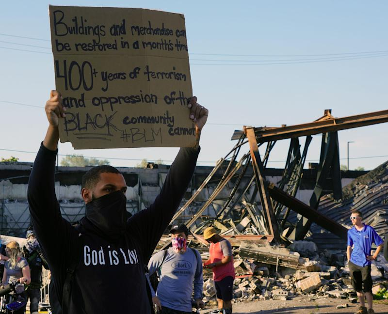 A protester argues that property damage can be repaired May 28 in front of a burned-out building in Minneapolis after the death of George Floyd.