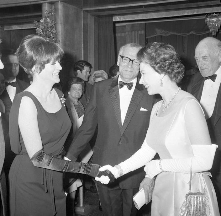 <p>Before she was damed by the Queen, Maggie Smith met the monarch at a charity premiere for her film <em>Othello</em>. Maggie wore a sophisticated black evening dress and a jeweled broach for the occasion, as one does.</p>