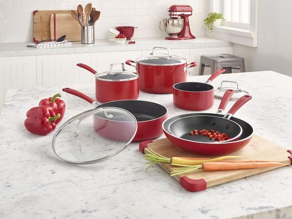 A red KitchenAid cooking set on display with two red peppers, a carrot, and a chopping board on a granite countertop.