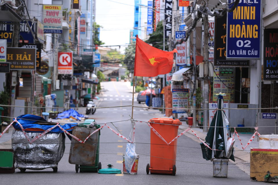 A street is blocked with carts and trash cans during a virus lockdown in Vung Tau, Vietnam on Sept. 13, 2021. More than a half of Vietnam is under a lockdown order to contain its worst virus outbreak yet. (AP Photo/Hau Dinh)
