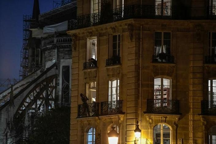 Neighbourgs talk to each other from their balconies in in Isle Saint-Louis in Paris, on the ninth day of the lockdown in France (AFP Photo/STEPHANE DE SAKUTIN)