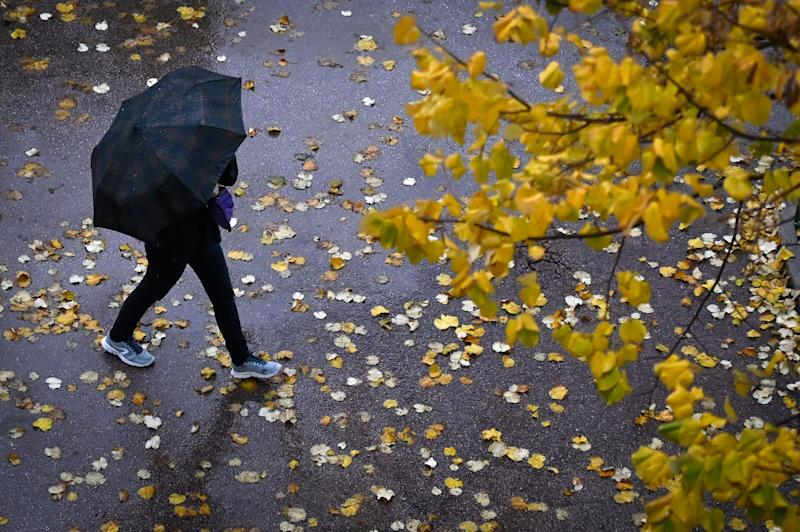 A person with an umbrella walks under the rain (AFP via Getty Images)