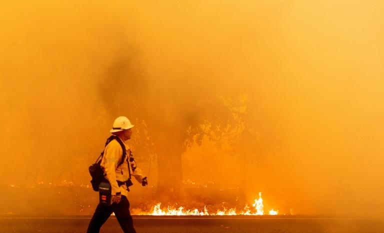 A Pacific Gas and Electric firefighter walks down a road as flames approach in Fairfield, California during the LNU Lightning Complex fire on August 19, 2020