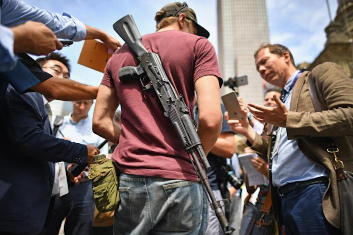 <p>Journalists talk with a man openly carrying a gun in downtown on the first day of the Republican National Convention on July 18, 2016, in Cleveland, Ohio. (Photo: Jeff J Mitchell/Getty Images)</p>