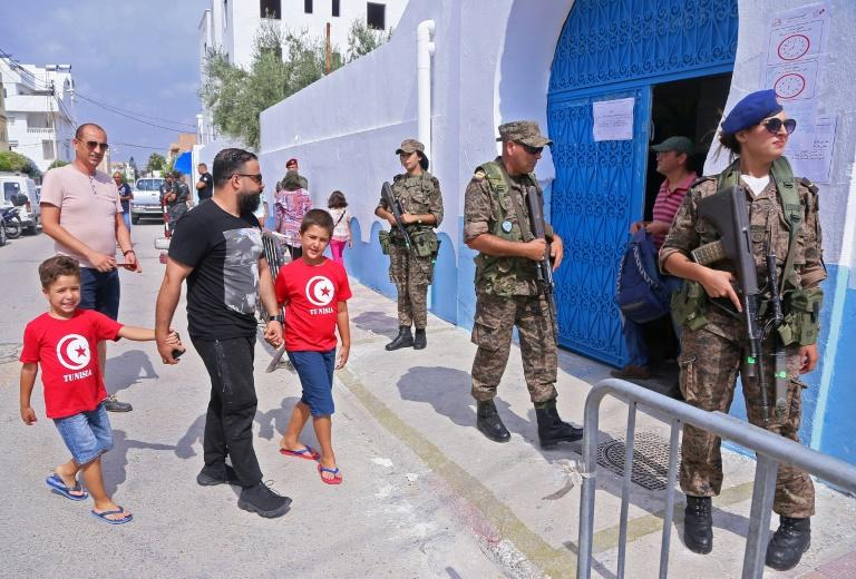 Tunisian soldiers stand guard outside a polling station as voters arrive to cast their ballots in Sousse on Sunday