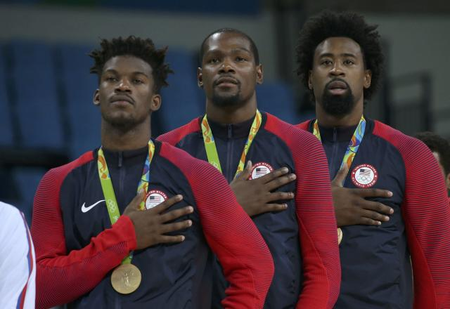 2016 Rio Olympics - Basketball - Final - Men's Gold Medal Game Serbia v USA - Carioca Arena 1 - Rio de Janeiro, Brazil - 21/8/2016. Jimmy Butler (USA) of the USA (L), Kevin Durant (USA) of the USA and Deandre Jordan (USA) of the USA (R) stand with their gold medals for the playing of the U.S. National Anthem during the presentation ceremony for men's basketball. REUTERS/Shannon Stapleton FOR EDITORIAL USE ONLY. NOT FOR SALE FOR MARKETING OR ADVERTISING CAMPAIGNS.