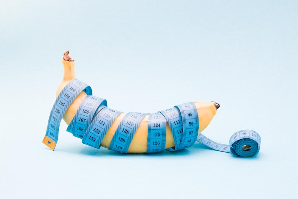ripe banana wrapped in blue measuring tape on a blue background copy space, diet concept, sex measurement concept, close up