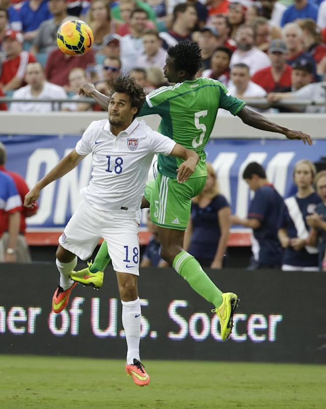 United States' Chris Wondolowski (18) heads the ball away from Nigeria's Efe Ambrose (5) during the second half of an international friendly soccer match in Jacksonville, Fla., Saturday, June 7, 2014. The United States won 2-1. (AP Photo/John Raoux)