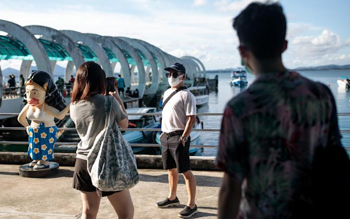 A domestic tourist wearing a face mask poses for a photo at the pier on Koh Samet - Jack Taylor